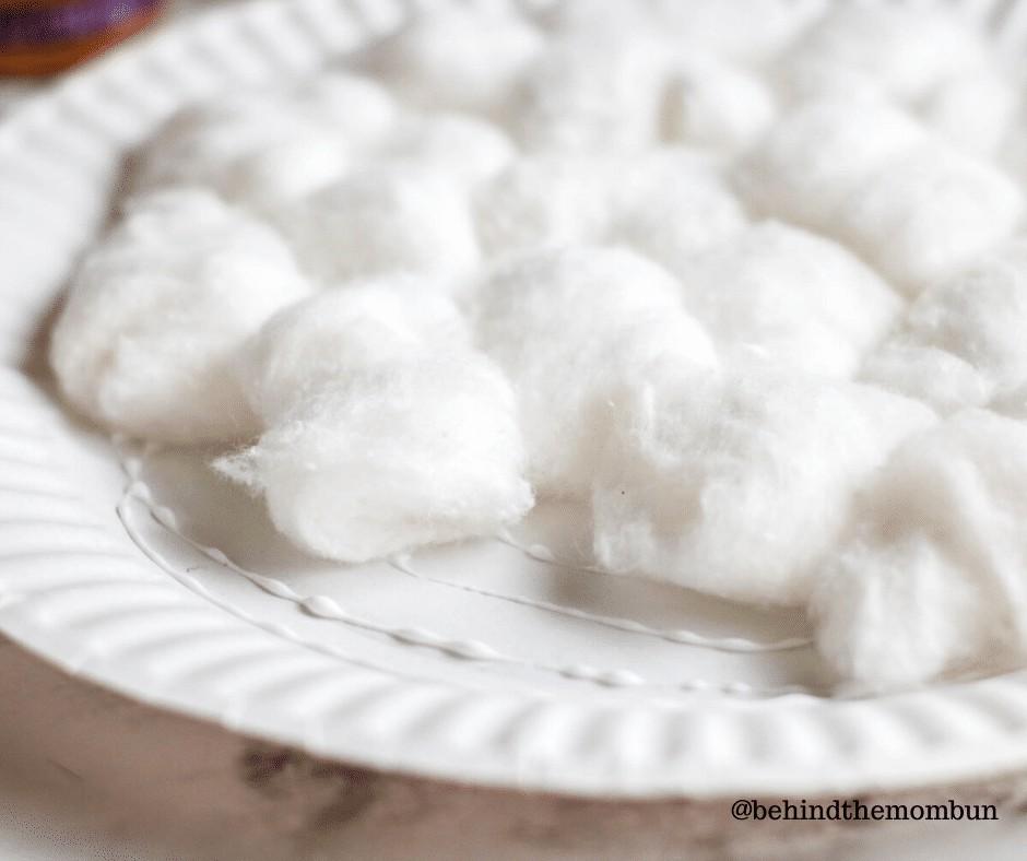 Cotton balls being glued on polar bear craft