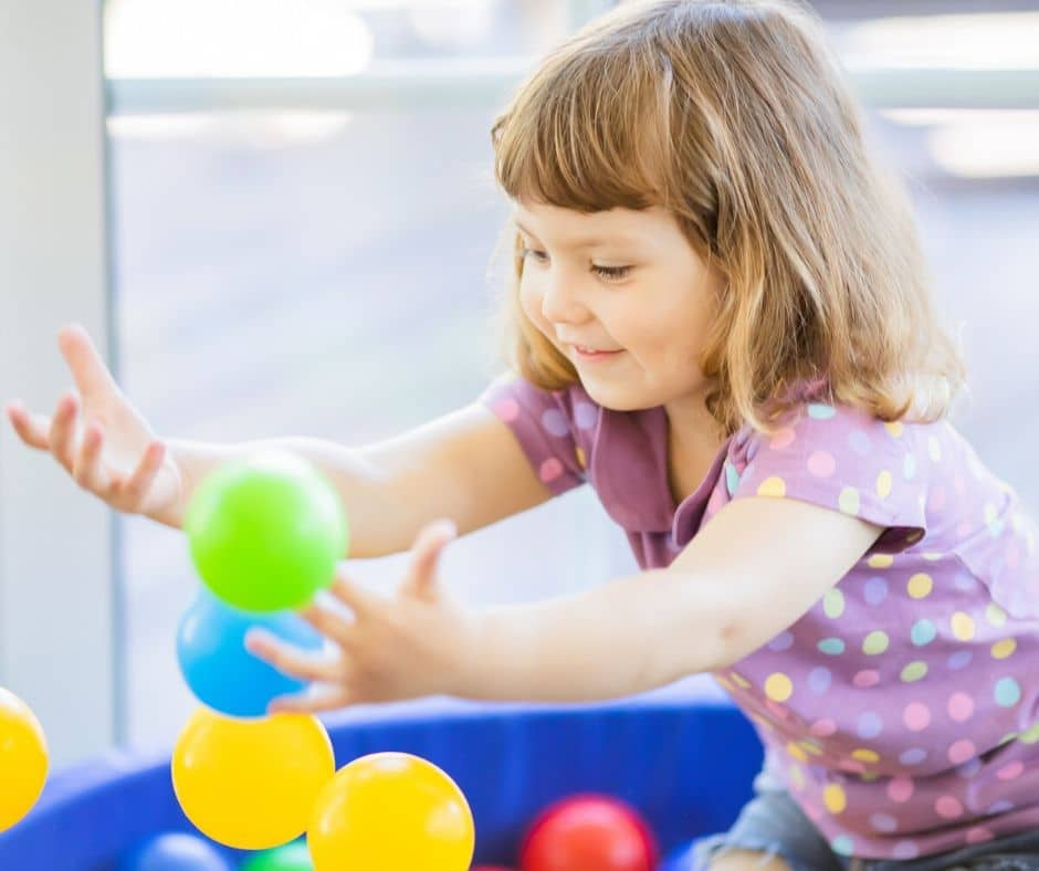 girl playing with colored balls